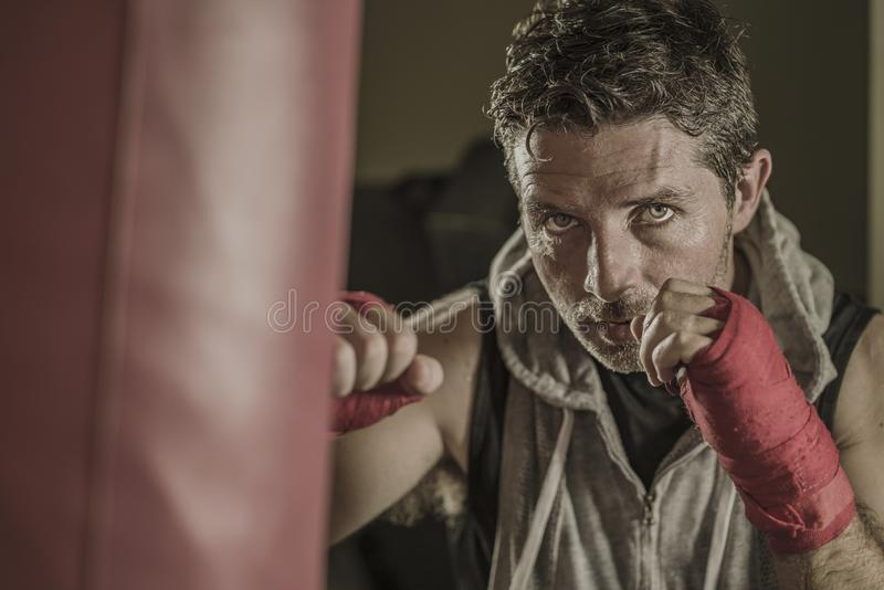 Lifestyle gym portrait of young attractive and fierce looking man training boxing at fitness club doing heavy bag punching workout royalty free stock photo