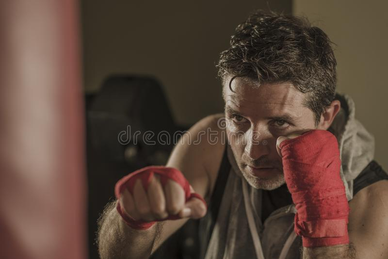 Lifestyle gym portrait of young attractive and fierce looking man training boxing at fitness club doing heavy bag punching workout royalty free stock photos