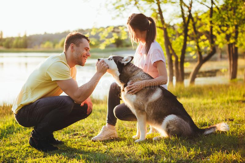 Lifestyle, happy family of two resting at a picnic in the park with a dog. royalty free stock photos