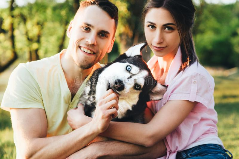 Lifestyle, happy family of two resting at a picnic in the park with a dog. royalty free stock image