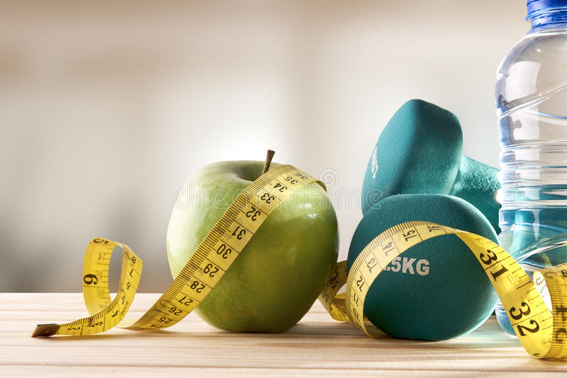 Lifestyle health diet and sports gym background front view. Dumbbells with apple, mineral water bottle and tape measure on wood table and gym background. Concept royalty free stock images