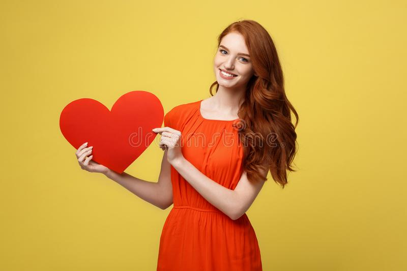 Lifestyle and Holiday Concept - Portrait Young happy red hair woman in orange beautiful dress holding big red heart stock images