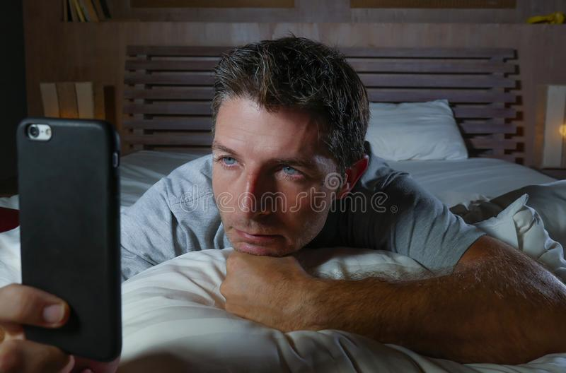 Lifestyle home portrait of young attractive and relaxed man using internet social media app on mobile phone in his bedroom late at. Night lying on bed stock photos