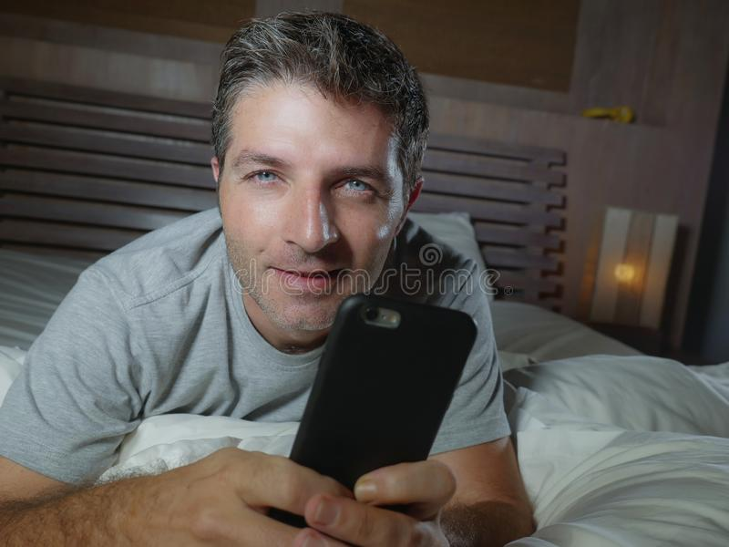 Lifestyle home portrait of young attractive and relaxed man using internet social media app on mobile phone in his bedroom late at. Night lying on bed stock image