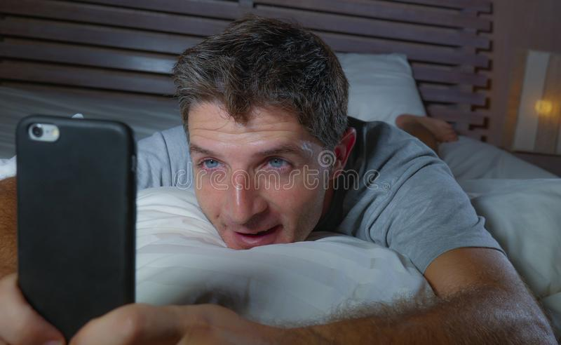 Lifestyle home portrait of young attractive and relaxed man using internet social media app on mobile phone in his bedroom late at. Night lying on bed stock images