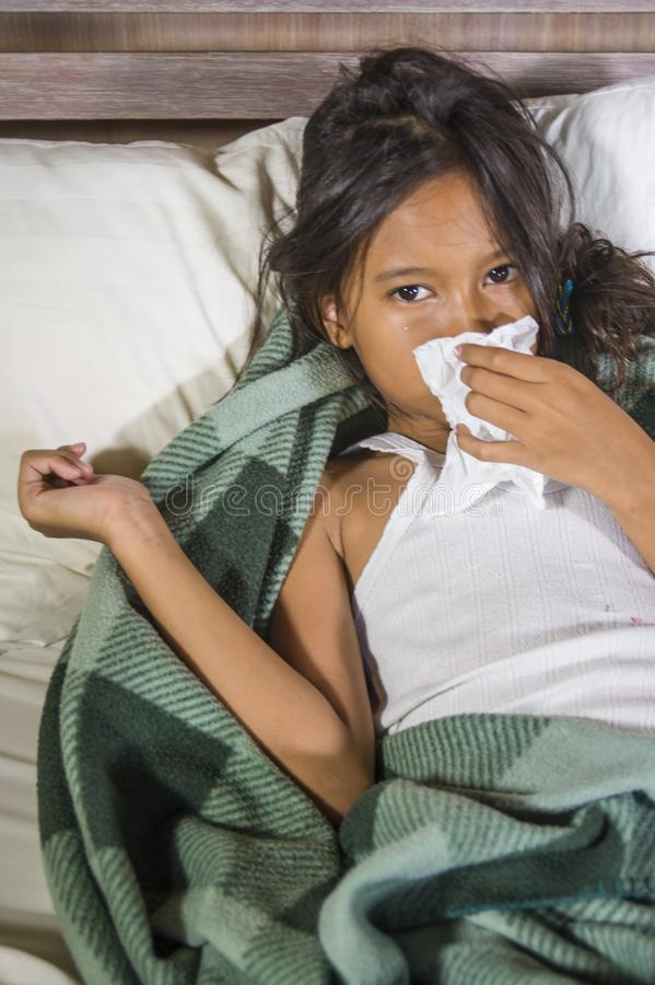 Lifestyle home portrait of young beautiful and sweet 8 years old female child holding tissue paper sneezing her nose lying sick on stock photography