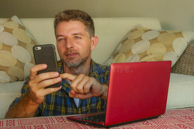 Lifestyle home portrait of young happy and attractive man at home sofa couch working on laptop computer using mobile phone relaxed. And cheerful smiling in stock photo