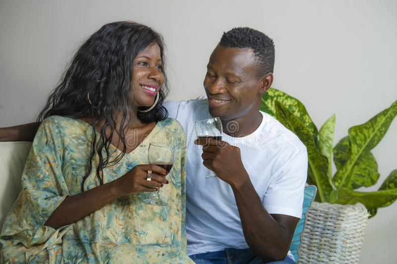 Lifestyle home portrait of young romantic and happy black African American couple in love drinking wine cup at living room couch stock images