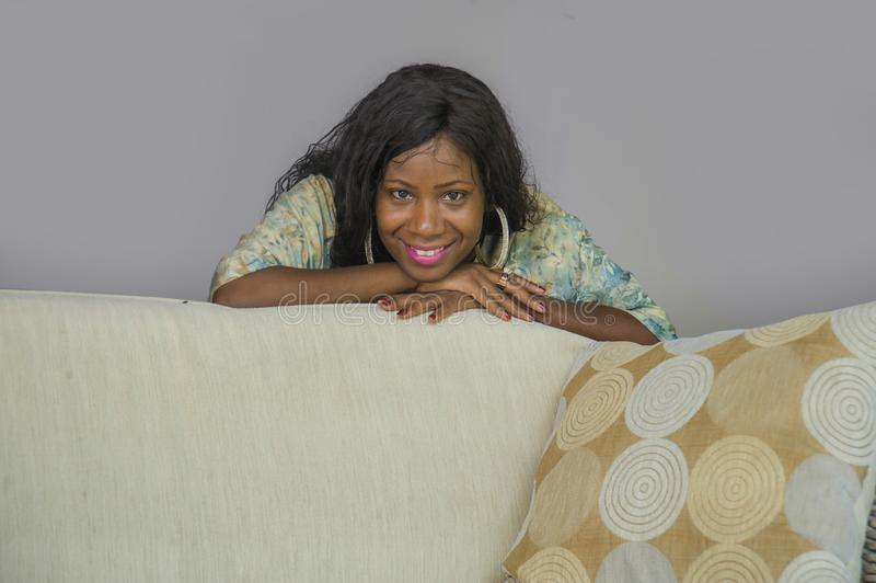 Young stylish beautiful and happy black afro American woman posing at living room sofa couch in her modern apartment smiling. Lifestyle home portrait of young stock photos