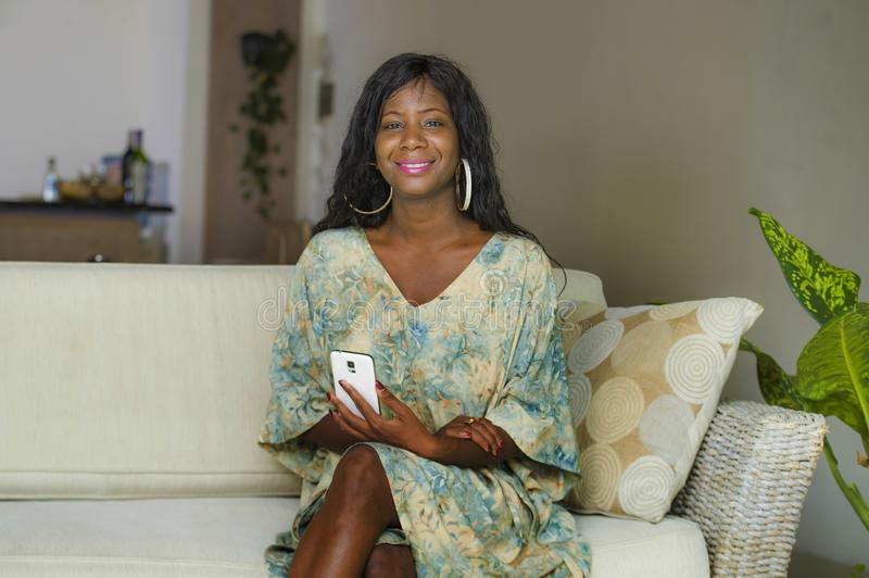 Young stylish beautiful and happy black afro American woman posing at living room sofa couch in her modern apartment using mobile. Lifestyle home portrait of royalty free stock images