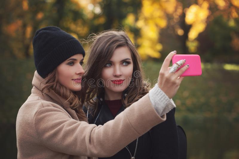 Lifestyle image of best friend girls taking selfie. Lifestyle image of best friend girls making selfie on smartphone camera outdoors, emotions and happy royalty free stock images