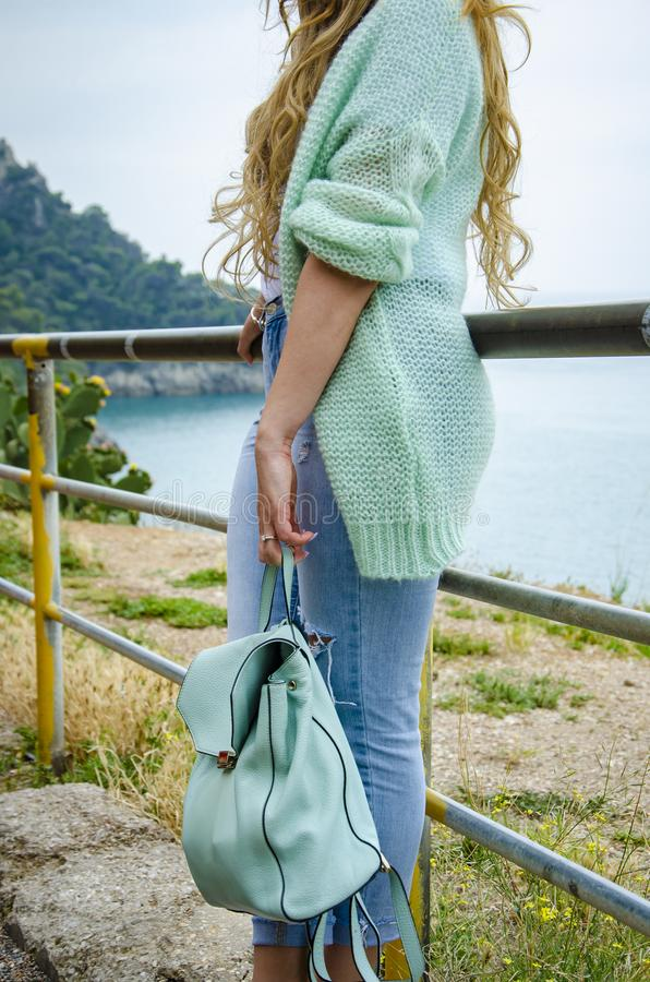 Lifestyle image of carefree traveling woman. On italian coast. Casual outfit. Oversize sweater, jeans and stylish accessories stock photos