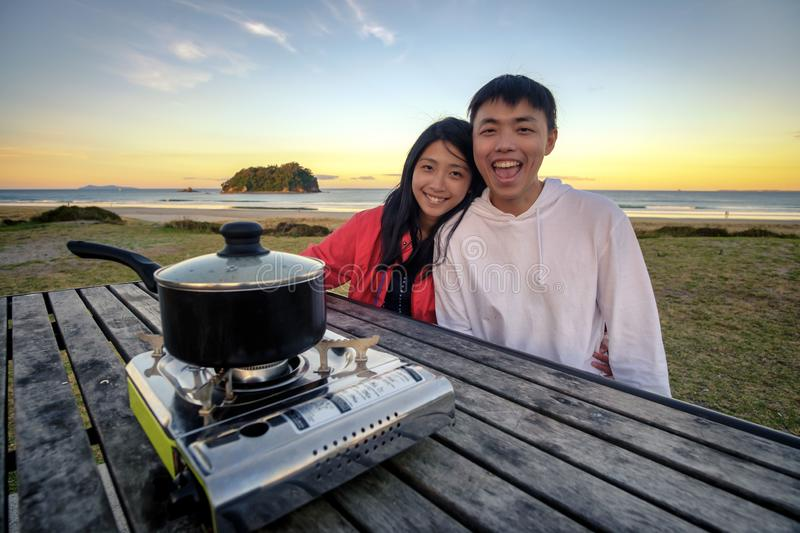 Lifestyle image of young happy asian couple eating hot pot stove on a table outdoor along beach. Leisure activity image of chinese. Couple holding chopsticks royalty free stock image