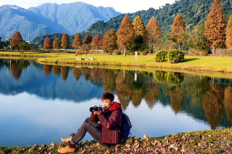 Lifestyle image of a young man enjoying photography. Lifestyle image of a young man enjoying photographing autumn scenery in Taiwan. Beautiful Taiwanese stock photo