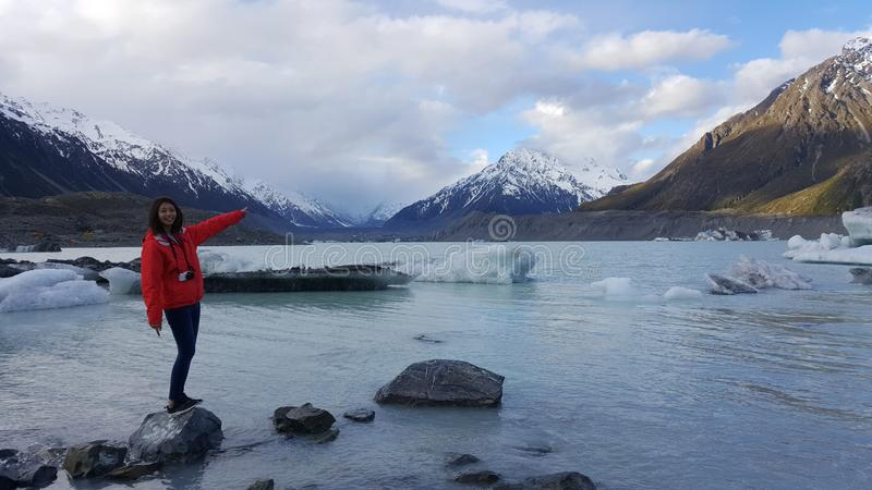 Lifestyle image of young woman enjoying beautiful winter landscape. New Zealand south island glacier. Cold winter landscape of ice on lake royalty free stock photo