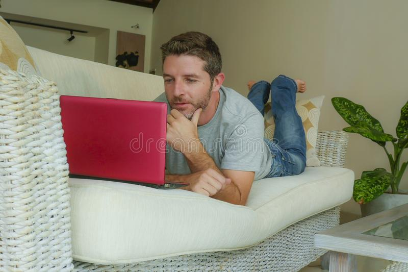 Young attractive and handsome happy man lying at home sofa couch working with laptop computer netbook relaxed in internet business. Lifestyle indoors portrait of stock image