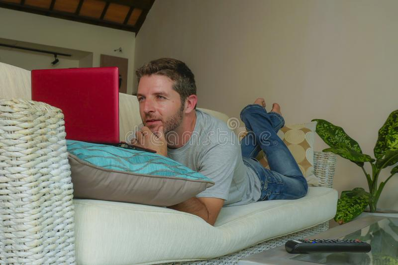 Young attractive handsome happy man lying at home couch working with laptop computer netbook relaxed in internet business concept. Lifestyle indoors portrait of stock photo