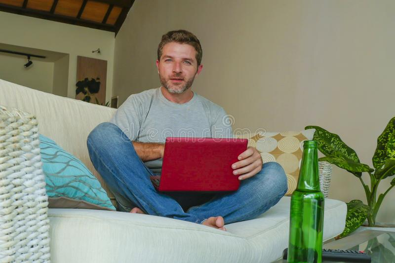 Lifestyle indoors portrait of young attractive and handsome happy man sitting at home sofa couch working online with laptop comput. Er using netbook relaxed royalty free stock photography