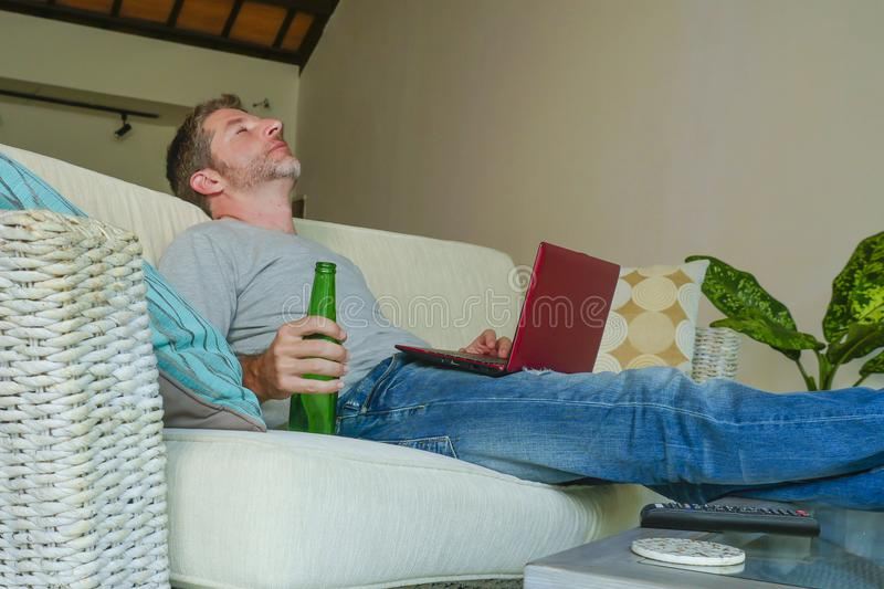 Lifestyle indoors portrait of young attractive and handsome happy man sitting at home sofa couch working online with laptop comput. Er using netbook relaxed stock images