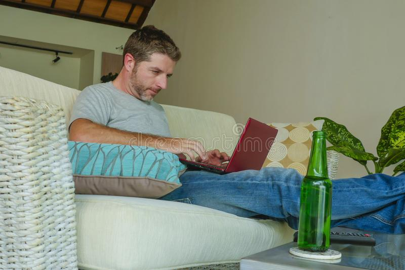 Lifestyle indoors portrait of young attractive and handsome happy man sitting at home sofa couch working online with laptop comput. Er using netbook relaxed stock photos