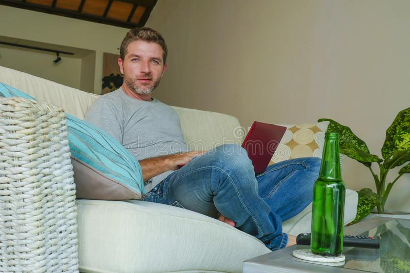 Lifestyle indoors portrait of young attractive and handsome happy man sitting at home sofa couch working online with laptop comput. Er using netbook relaxed royalty free stock photos