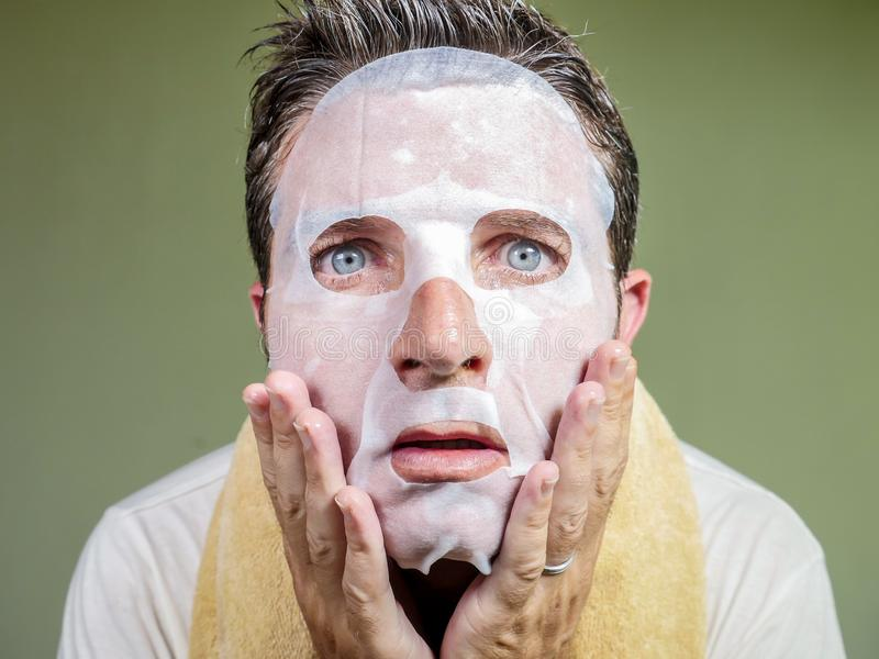 Lifestyle isolated background portrait of young weird and funny man at home trying using beauty paper facial mask cleansing royalty free stock photo