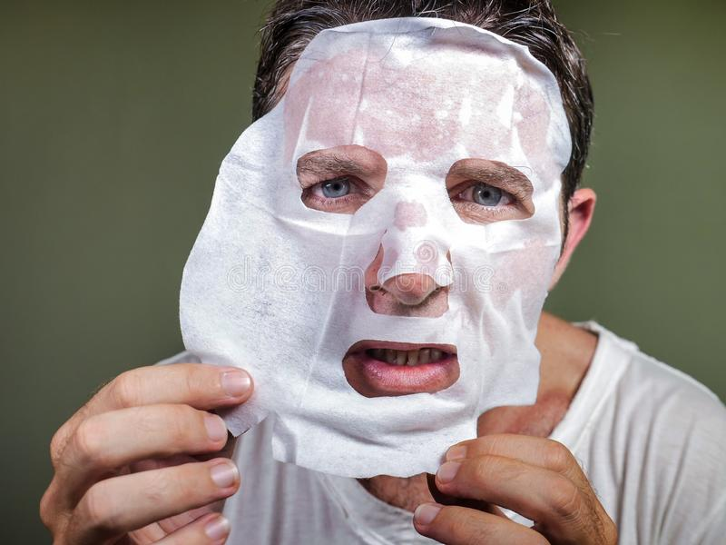 Lifestyle isolated background portrait of young weird and funny man at home trying using paper facial mask cleansing applying anti royalty free stock photography
