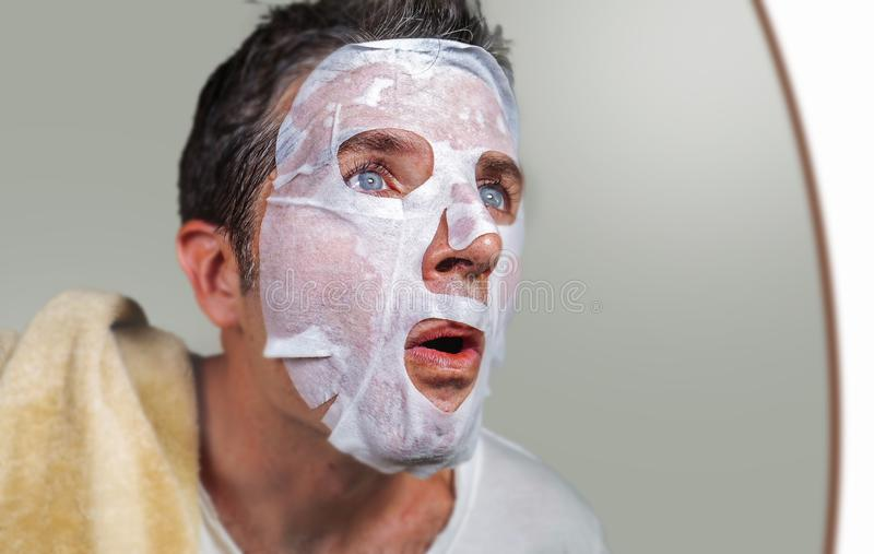 Lifestyle isolated background portrait of young weird and funny man at home trying using paper facial mask cleansing applying anti stock photos