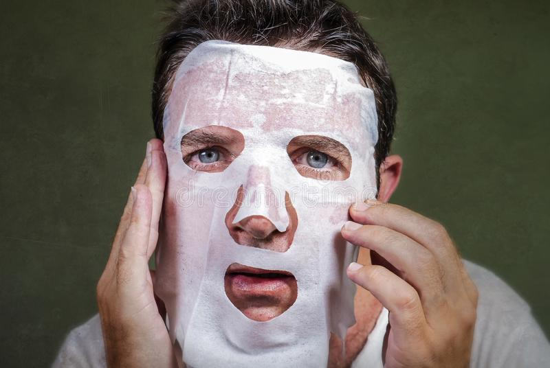 Lifestyle isolated background portrait of young weird and funny man at home trying using paper facial mask cleansing applying anti stock images