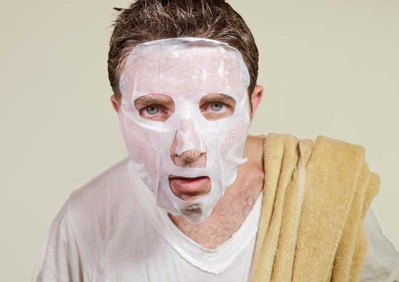 Lifestyle isolated background portrait of young weird and funny man at home trying using paper facial mask cleansing applying anti stock photo