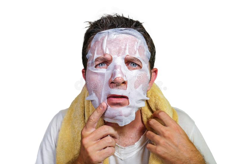 Lifestyle isolated background portrait of young weird and funny man at home trying using paper facial mask cleansing applying anti stock photography