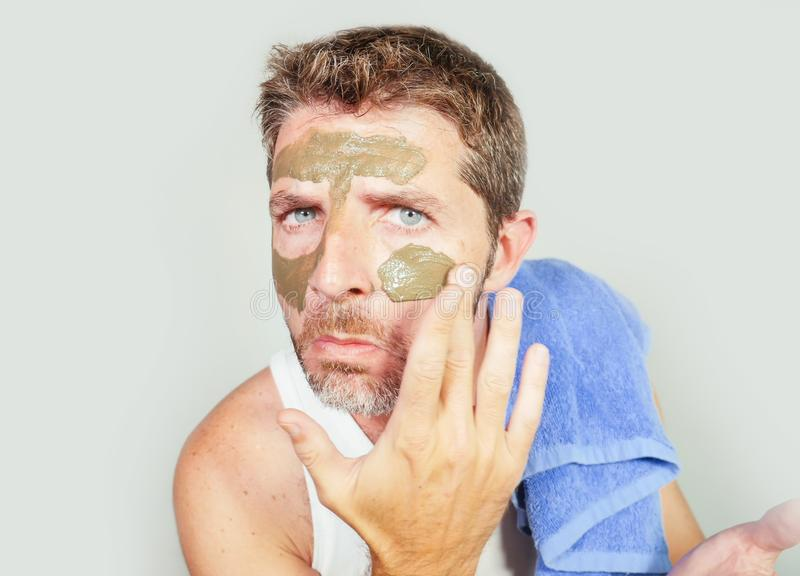 Lifestyle isolated portrait of young attractive and happy man with bathroom towel applying with green cream on his face applying stock photo