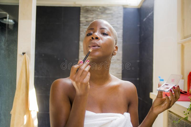 Lifestyle natural portrait of young attractive and happy black african American woman at home bathroom applying face makeup with b. Rush looking at toilet mirror stock images