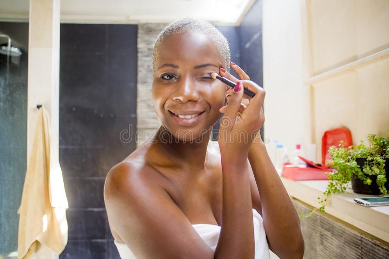 Lifestyle natural portrait of young attractive and happy black african American woman at home bathroom applying face makeup with b. Rush looking at toilet mirror royalty free stock photo
