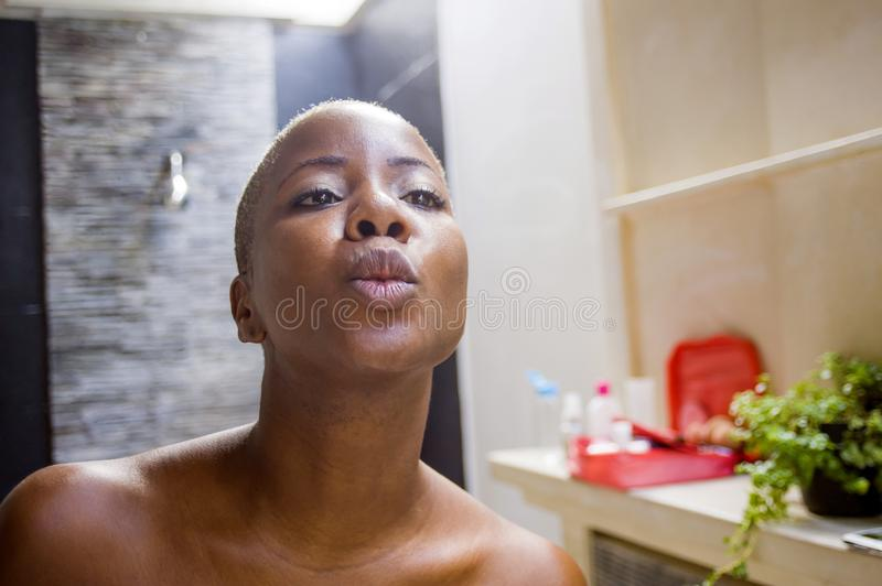 Lifestyle natural portrait of young attractive and happy black afro American woman at home bathroom looking at mirror with kissing stock photos