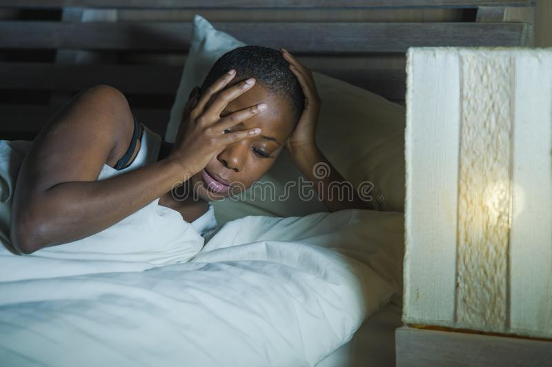 Lifestyle night portrait of young sad and stressed black african American woman lying on bed upset trying to sleep suffering insom royalty free stock photos