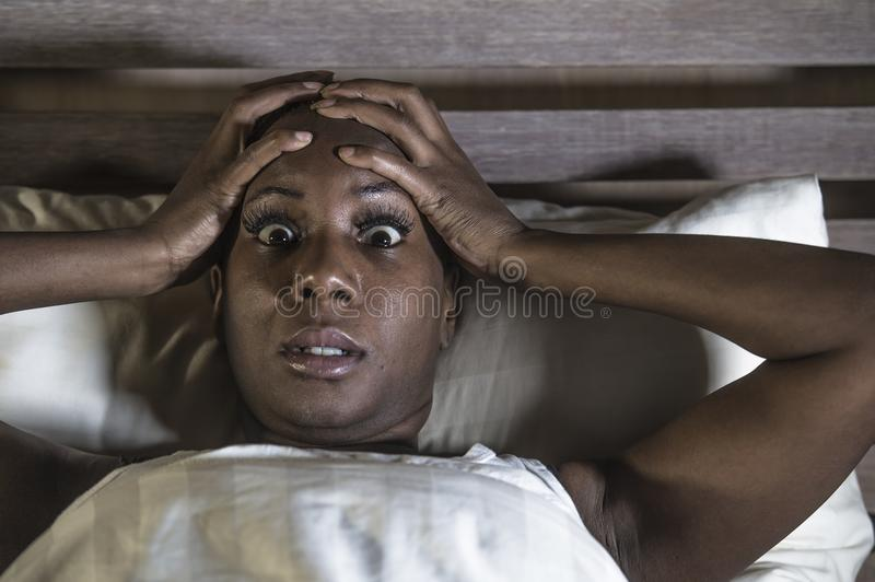 Lifestyle night portrait of young scared and stressed black afro American woman depressed on bed upset unable to sleep suffering h. Angover headache feeling sick royalty free stock photography