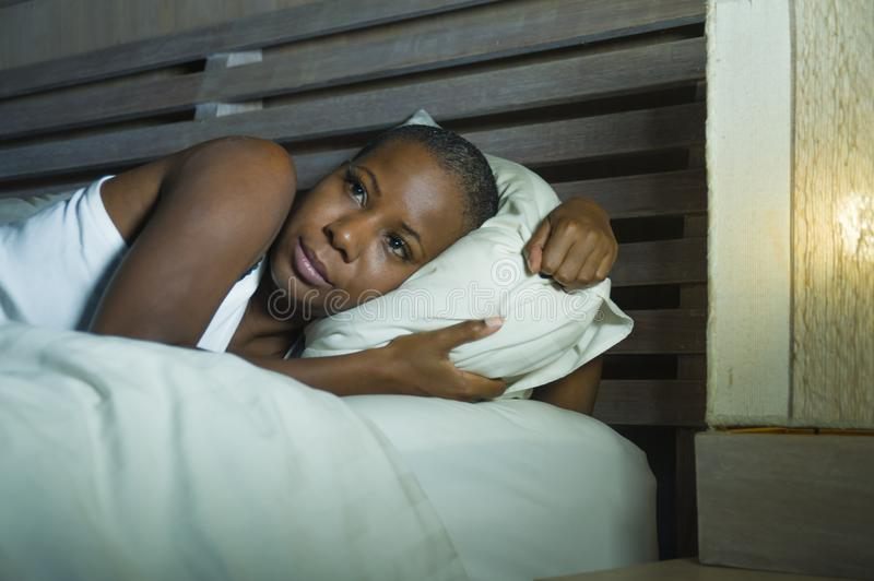 Lifestyle night portrait of young scared and stressed black afro American woman depressed on bed upset unable to sleep suffering h. Angover headache feeling sick royalty free stock image