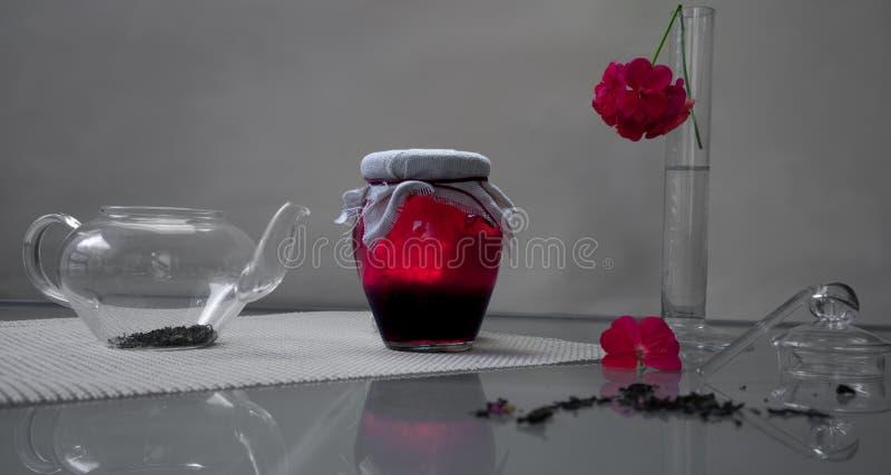 lifestyle O banco do doce de framboesa com chá e o pelargonium florescem em uma tabela de vidro fotos de stock royalty free