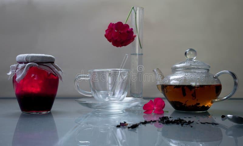 lifestyle O banco do doce de framboesa com chá e o pelargonium florescem em uma tabela de vidro foto de stock royalty free