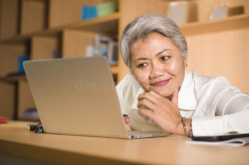 Lifestyle office portrait of attractive and happy successful middle aged Asian woman working at laptop computer desk smiling stock images