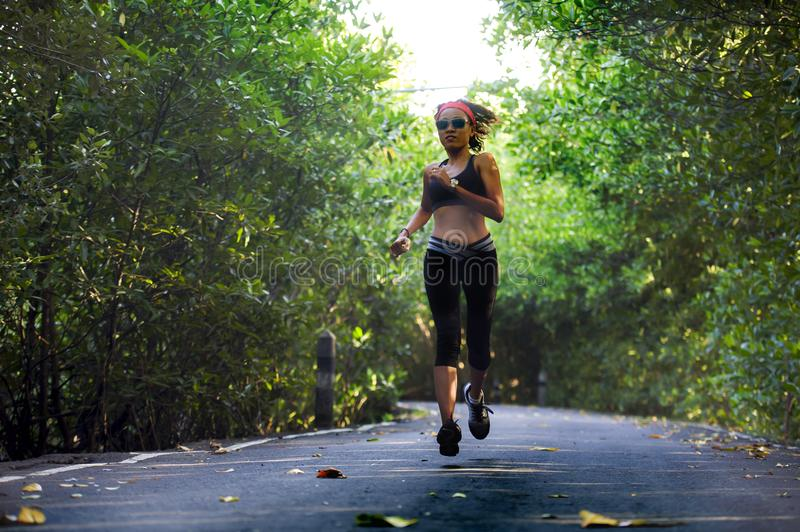 Lifestyle outdoors portrait of young attractive and fit woman with hairband training asphalt road running workout at beaut. Iful trees city park in exercise royalty free stock photography
