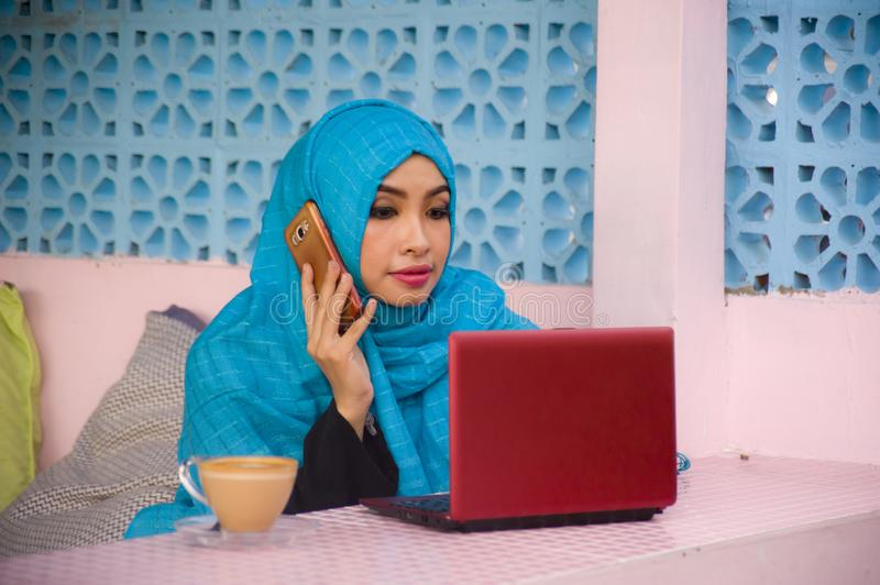 Young beautiful and happy woman in muslim hijab head scarf working with laptop computer and mobile phone networking running inter stock photo