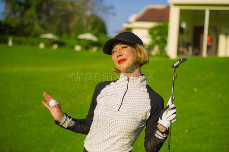 Lifestyle outdoors portrait of young beautiful and happy woman at playing golf holding ball and putter club smiling cheerful in st royalty free stock photography