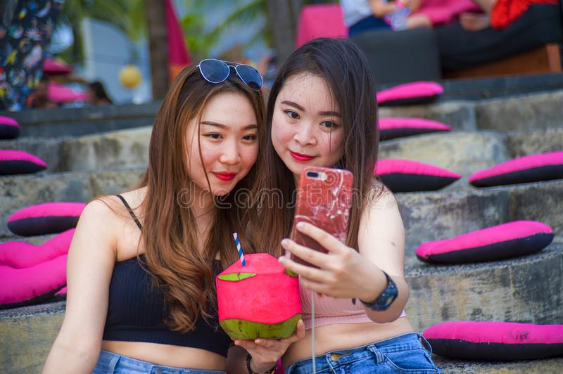 Lifestyle outdoors portrait of young happy and beautiful Asian Chinese girls taking selfie picture with mobile phone enjoying holi stock photo