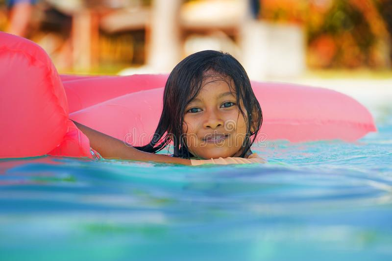 Lifestyle outdoors portrait of young happy and cute female child having fun with inflatable airbed in holidays resort swimming royalty free stock image