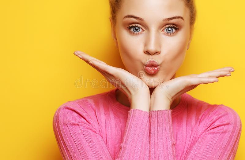 Lifestyle and people concept - Beautiful blond woman with kiss gesture. stock photos