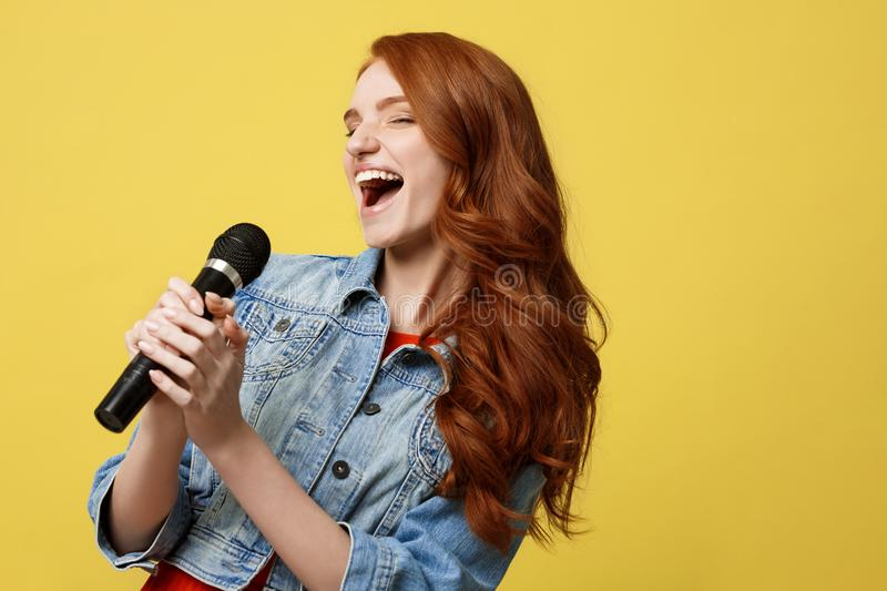 Lifestyle and People Concept: Expressive beauty ginger hair model girl in casual jean cloth singer with a microphone. stock photos
