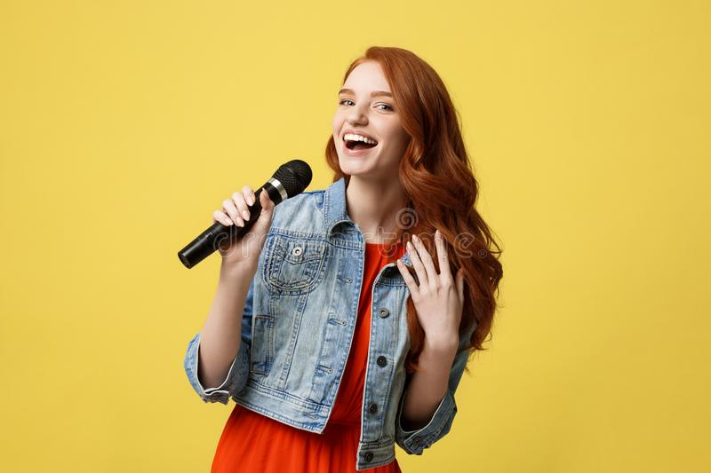 Lifestyle and People Concept: Expressive beauty ginger hair model girl in casual jean cloth singer with a microphone. stock photo