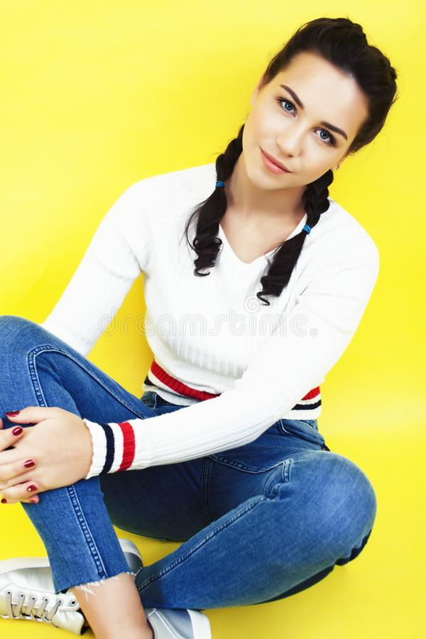 Lifestyle people concept: pretty young school teenage girl having fun happy smiling on yellow background close up stock photography